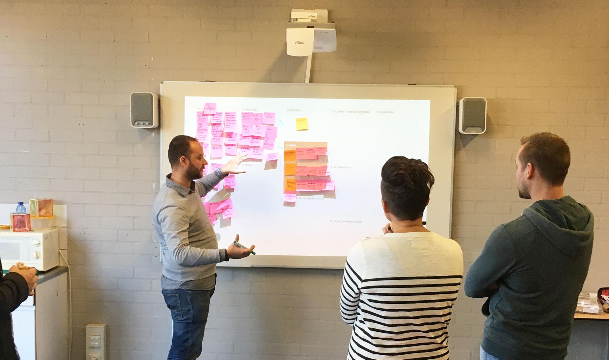 Designers bespreken schetsen bij whiteboard